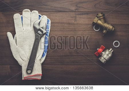 adjustable wrench gloves and pipes on the wooden background