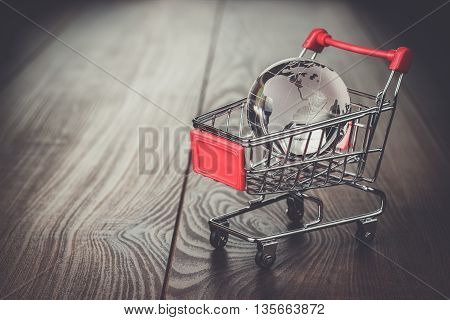 glass globe in the shopping trolley global market concept