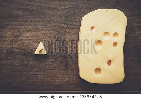 small and big pieces of cheese on wooden table