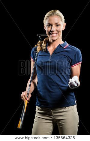 Portrait of golf player holding a golf club and golf ball on black background