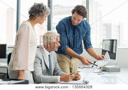 Business team meeting for financial report. Young employee briefing with senior leadership and businesswoman about new project. Business partners in a conversation over future growth.