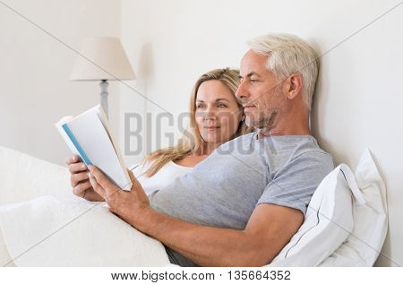 Senior couple reading a book in bed before going to sleep. Relaxed senior man and smiling woman reading together a book lying on bed. Retired man reading a book to his wife in their home.
