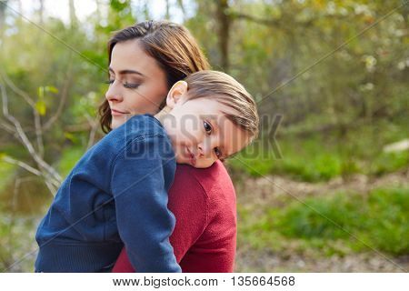Mother holding kid boy tired in her shoulder at park