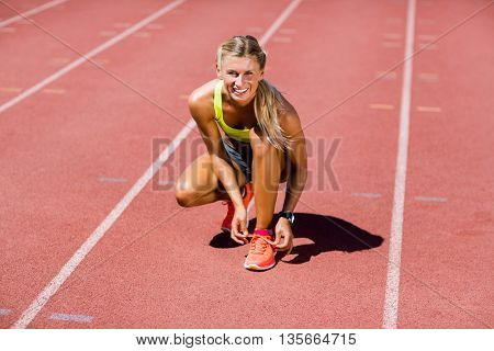 Portrait of female athlete tying her shoe laces on running track on a sunny day