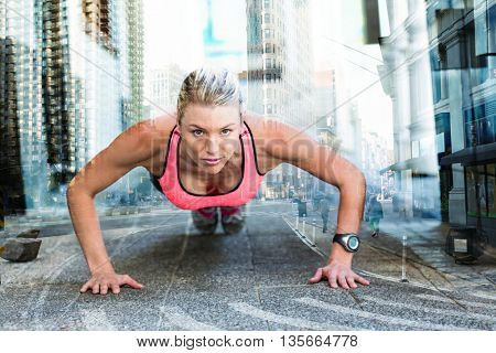 A pretty woman doing push-ups on the floor against new york street