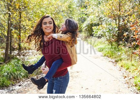 Mother and daughter piggyback in a park playing having fun