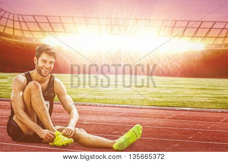 Sportsman smiling and lacing shoes against race track