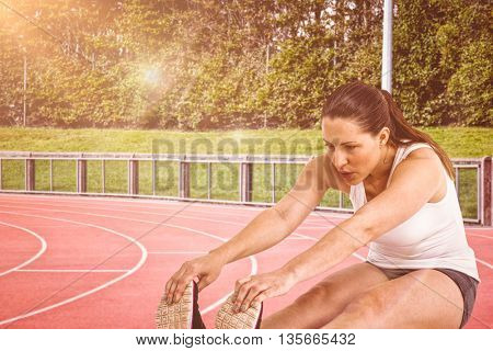 Athlete woman doing stretching exercise against race track