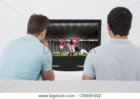 Two soccer fans watching tv against rugby players tackling during game