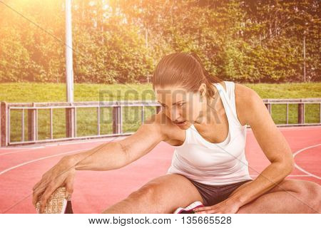 Athlete woman stretching her hamstring against race track