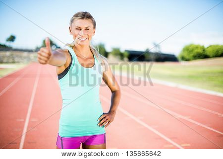 Happy female athlete showing thumbs up on running track