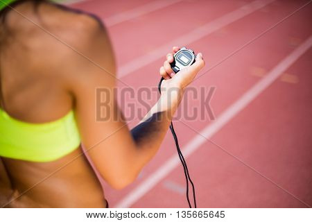 Mid-section of female athlete checking her smart watch on running track