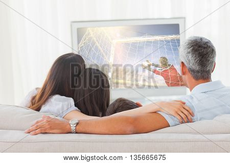 Football player kicking ball against family watching television together on sofa