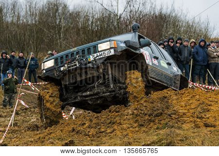 Lviv Ukraine - February 21 2016: Off-road vehicle brand Jeep Cherokee overcomes the track on a amateur competitions Trial near the city Lviv Ukraine. Audience watching the competitions.