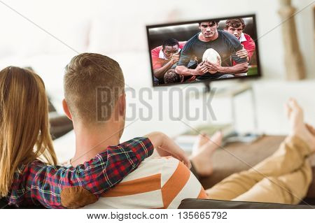 Cute couple relaxing on couch against rugby players tackling during game
