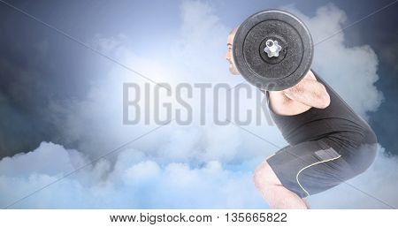 Bodybuilder lifting heavy barbell weights against cloudy sky