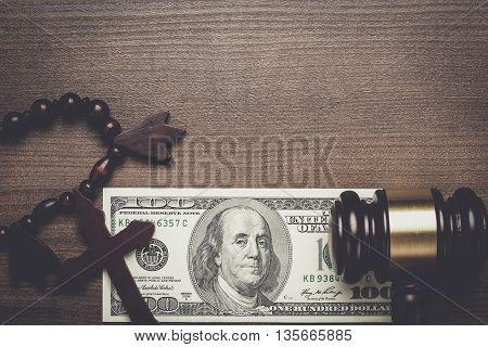 wooden cross gavel and money on brown table background concept