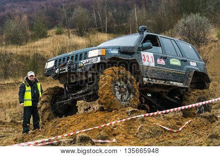 Lviv Ukraine - February 21 2016: Off-road vehicle brand Jeep Cherokee overcomes the track on a amateur competitions Trial near the city Lviv Ukraine. Referee watching the competitions.