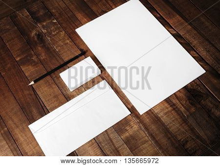 Photo of blank stationery and corporate identity set on vintage wooden table background: letterhead business cards envelope and pencil. Blank mock-up for your design.