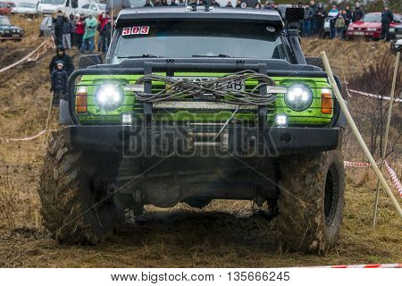 Lviv Ukraine - February 21 2016: Off-road vehicle brand Nissan overcomes the track with headlights on a amateur competitions Trial near the city Lviv Ukraine. Audience watching the competitions.