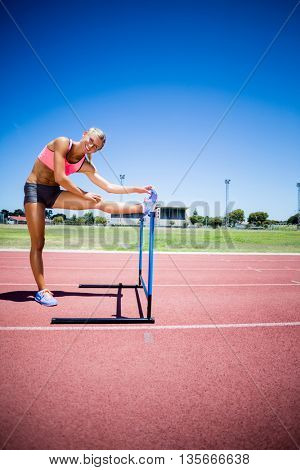 Portrait of female athlete warming up in stadium on a sunny day