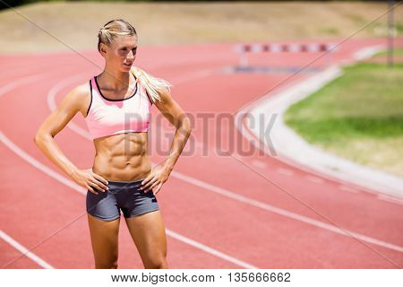 Female athlete standing with hands on hip on the running track on a sunny day