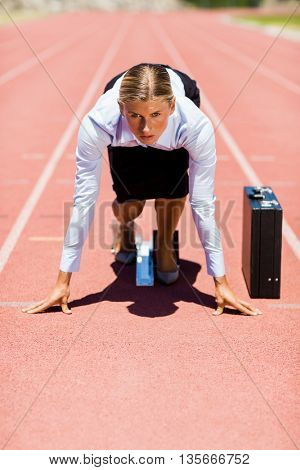 Businesswoman with briefcase ready to run on running track