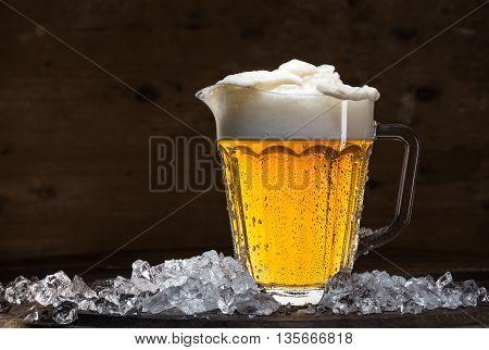 Pitcher of beer on ice, dark background