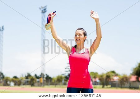 Female athlete waving her hand and showing gold medal in stadium