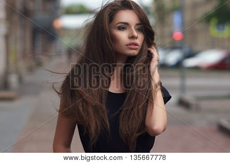 Fashion style portrait of young beautiful elegant woman in black dress walking at city streets on a windy dull day.