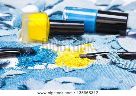 Close-up of makeup brushes, crushed compact blue and yellow eyeshadow with nail polishes of the same colors surrounded by rags of denim. Side view, shallow depth of field