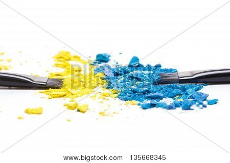 Close-up of makeup brushes with crushed compact blue and yellow eyeshadow on white background. Side view, shallow depth of field. Modern stylish eye makeup