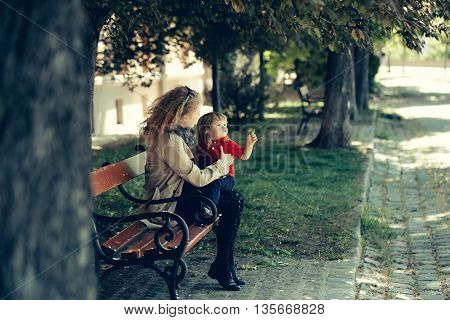 Girl and little boy on the wooden bench. The boy points at something.