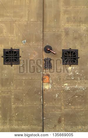 Gothic medieval iron armor door decorated with small square grating windows and doorknob background