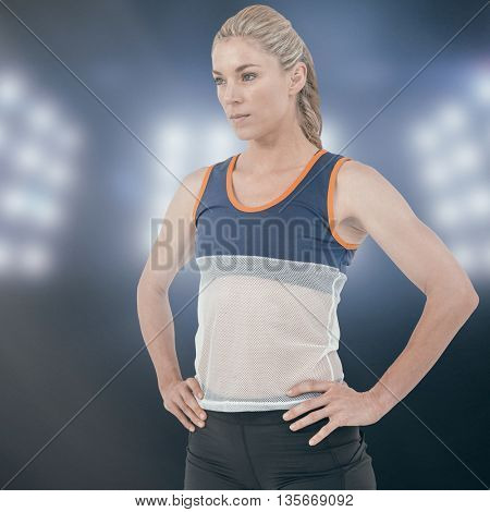Female athlete standing with hand on hip against composite image of spotlight