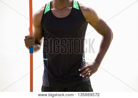 Mid section of athlete standing with javelin in stadium