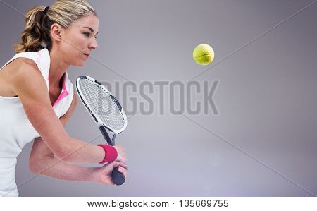 Athlete playing tennis with a racket against grey background