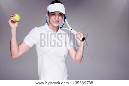 Female athlete playing tennis against grey background