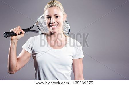 Portrait of female tennis player posing with racket against grey background