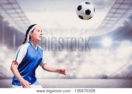 Woman soccer player waiting the ball against sports arena