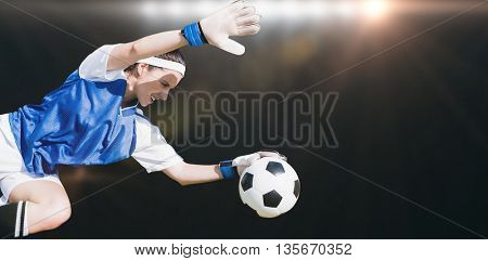 Woman goalkeeper stopping a goal against spotlight
