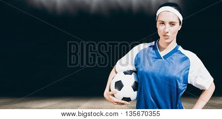 Woman football player posing with football on a white backgorund against football pitch at night with lights