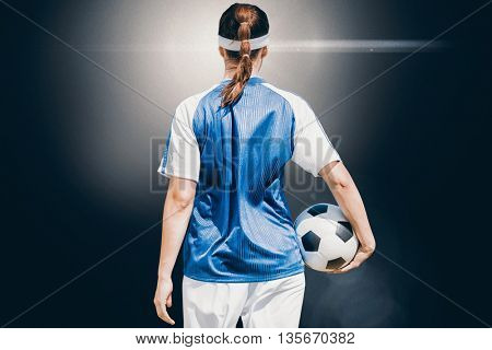 Rear view of woman soccer player holding a ball against view of lighting