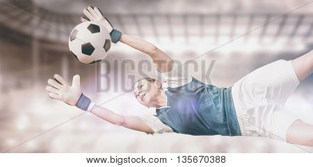 Woman goalkeeper stopping a goal against sports arena