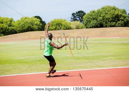 Athlete about to throw a javelin in the stadium