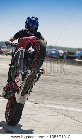 VinnytsiaUkraine-July 25 2015: Unknown stunt biker entertain the audience before the start of the championship of drifting on July 252015 in Vinnytsia Ukraine.