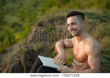Young handsome smiling man with muscular sexy body and bare chest sitting with laptop outdoor sunny day