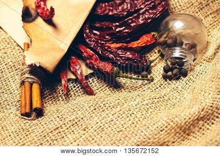 brown scorched paper envelope with dried red wrinkled chilli pepper inside with cinnamon and light bulb on burlap background copy space
