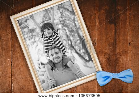 Father carrying a happy son on shoulders at park against white background with vignette
