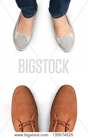 Casually dressed womans feet against focus of dress shoes